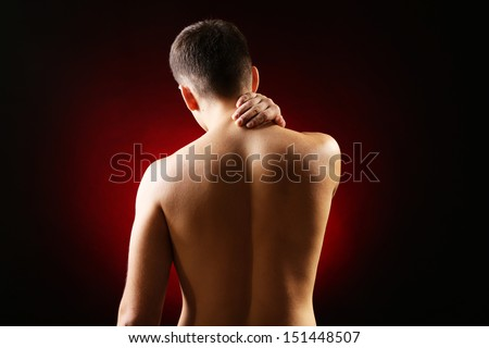 Young man with neck pain, on red background