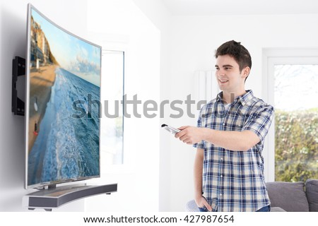 Young Man With New Curved Screen Television At Home - stock photo