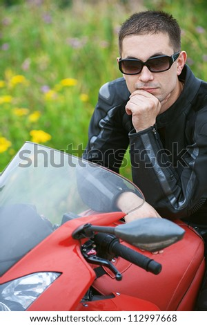 Young man with nice bike on road. - stock photo
