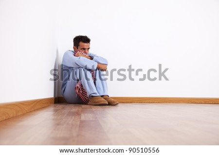 Young man with nightclothes sit at the room corner with fear - stock photo