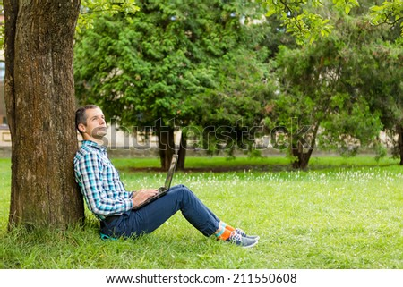Young man with notebook working in the park - stock photo