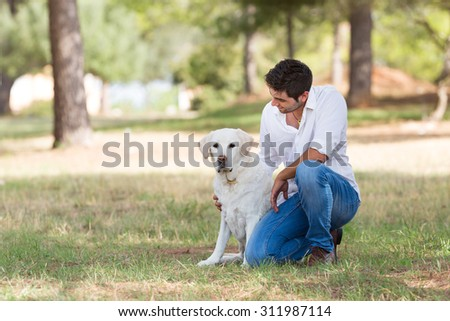young man with old senior labrador dog in the nature, selective focus