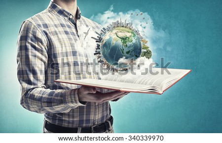 Young man with opened book in hands. Elements of this image are furnished by NASA - stock photo