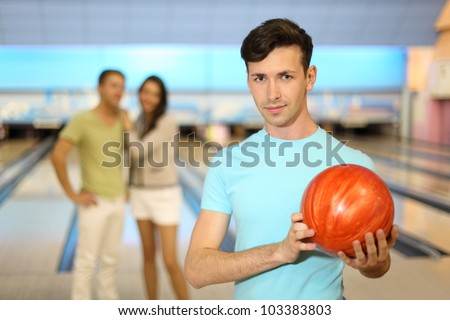 Young man with orange ball; couple stands behind him in bowling club; focus on right man; shallow depth of field