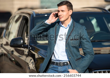 Young man with phone leaned on his car. Concept for car rental - stock photo