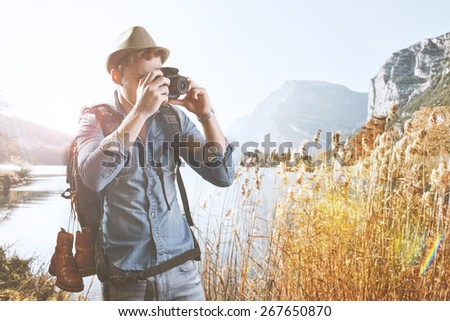 Young Man with photo camera outdoor with mountains winter nature on background - stock photo