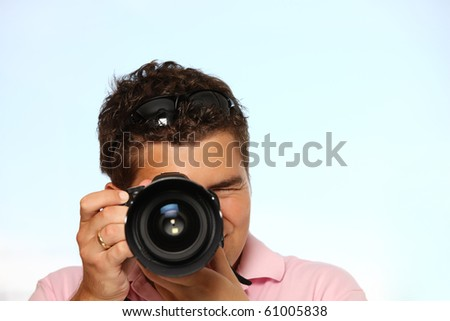 Young man with photo camera taking pictures