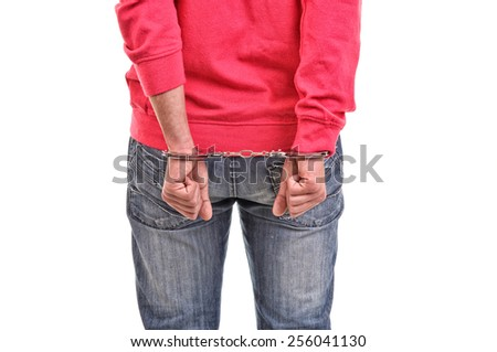 young man with pink blouse handcuffed with hands behind his back - stock photo