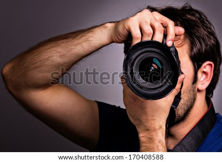 Young man with professional camera isolated on gray background. - stock photo