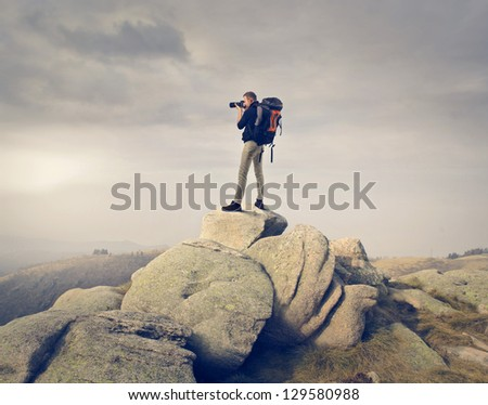 young man with professional camera photographing the landscape - stock photo