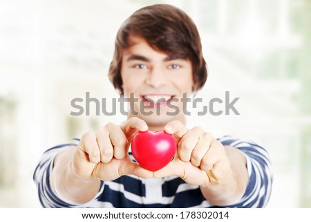 Young man with red heart. - stock photo