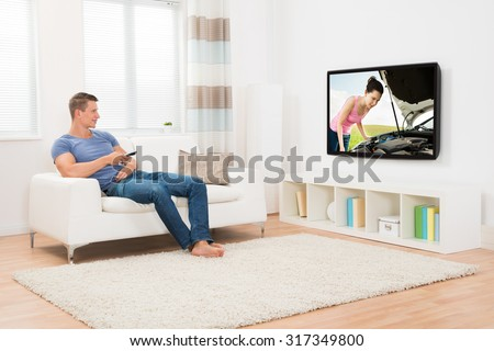 Young Man With Remote Control Watching Television In Living Room - stock photo