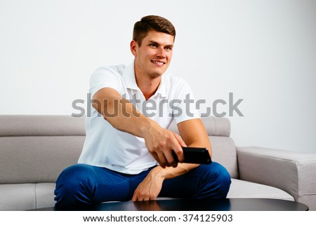 Young man with remote watching TV