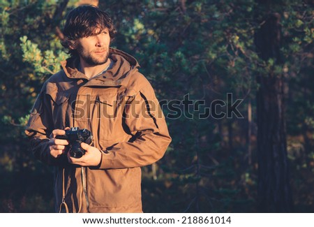 Young Man with retro photo camera outdoor hipster Lifestyle forest nature on background - stock photo