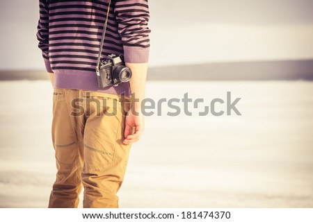 Young Man with retro photo camera outdoor hipster Lifestyle with nature on background  - stock photo