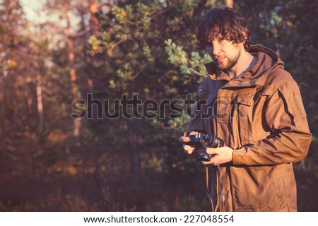 Young Man with retro photo camera outdoor Travel Lifestyle forest nature on background - stock photo