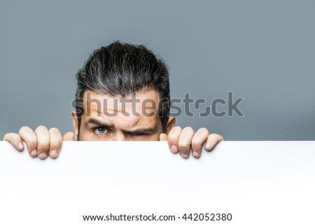 young man with scared eyes on emotional face with long hair behind white paper sheet in studio on grey background, copy space