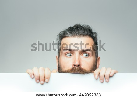 young man with scared face with long hair behind white paper sheet in studio on grey background, copy space