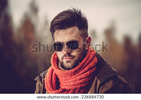 Young man with scarf and sunglasses in winter