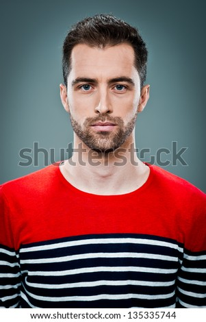 Young Man with Serious Expression over a Grey Background - stock photo