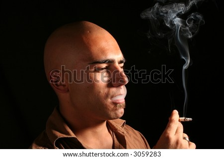 young man with shaved head smoking cigarette