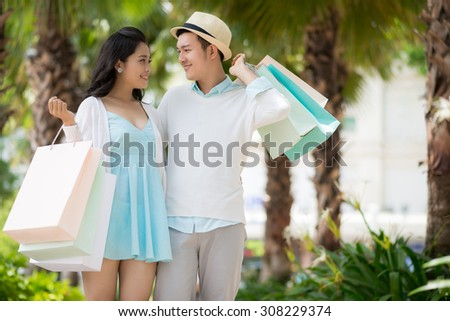 Young man with shopping bags looking at his beautiful girlfriend - stock photo