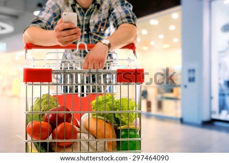 Young man with shopping cart in store - stock photo