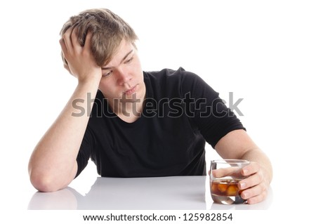 Young man with short blond hair and a black T-shirt sits at a table and holding an empty beer bottle in his hand, isolated against a white background. - stock photo