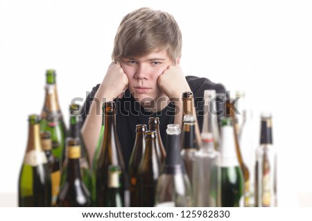 Young man with short blond hair lying on the floor and is surrounded by many empty beer and liquor bottles, isolated against white background. - stock photo