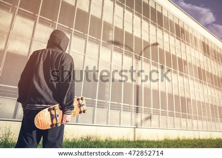 Young man with skateboard on city town background. Fashion Free Relax Skateboard Trendy Teenager Concept. Youth skateboard subculture.