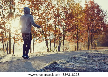 Young man with skipping rope in park during fall - stock photo