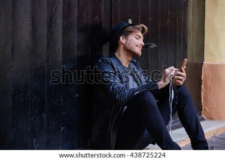 Young man with smartphone earphones sitting in the street black door - stock photo