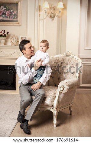 Young man with son sitting in armchair in living room - stock photo