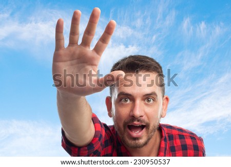 Young man with squares shirt over clouds background. Stopping someone