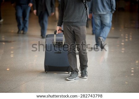 Young man with suitcase walking in modern airport terminal with crowd on background, wearing casual style clothes, close up
