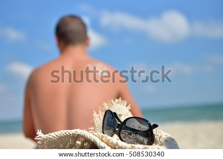 Young man with sun cream on his back stands to sunbath on the beach, focus on the straw hat and glasses. Sunscreen lotion on beach. Healthy skin. Summer vacation. Sea in the background