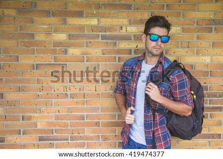 Young man with sunglasses and shirt carrying a bag. He is standing leaning against a brick wall.
