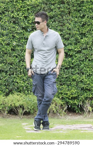 Young man with Sunglasses lifestyle vintage in the garden. - stock photo