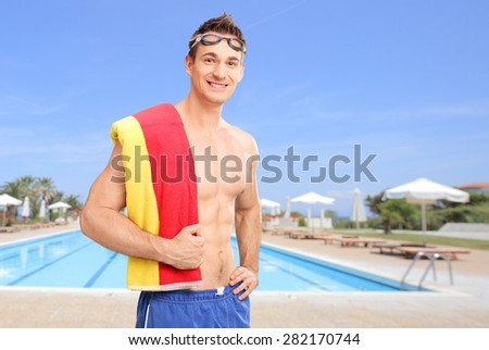 Young man with swimming goggles carrying a towel over his shoulder and posing in front of a swimming pool - stock photo
