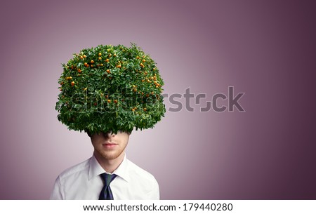 Young man with tangerine tree instead hair - stock photo