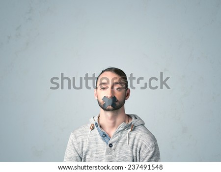 Young man with taped mouth. Isolated on gray background - stock photo