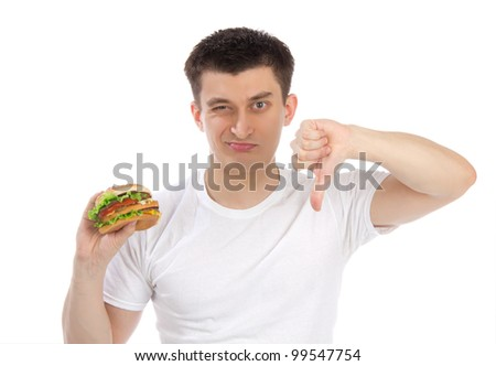 Young man with tasty fast food unhealthy burger in hand getting ready to eat isolated on a white background