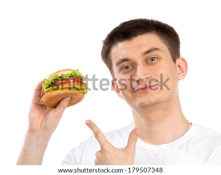 Young man with tasty fast food unhealthy burger sandwich in hand getting ready to eat isolated on a white background - stock photo