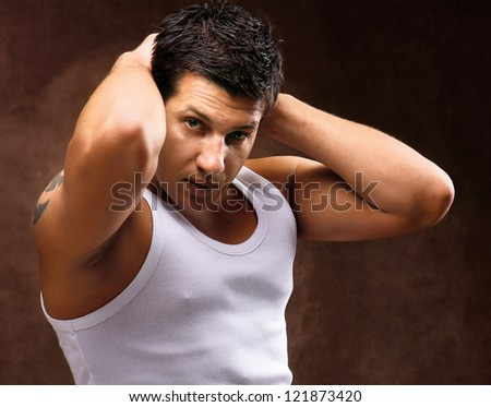Young man with tatoo posing against brown background - stock photo