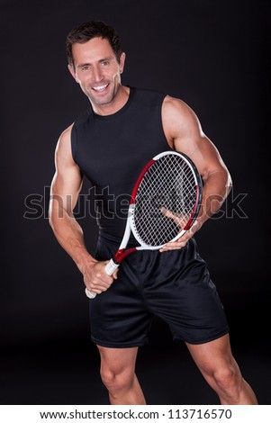 Young Man With Tennis Racket Isolated On Black Background - stock photo