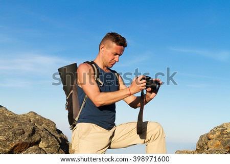 young man with the camera among rocks
