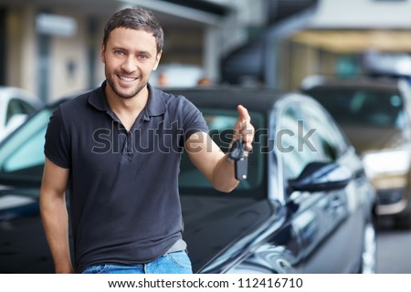 Young man with the keys at the car - stock photo