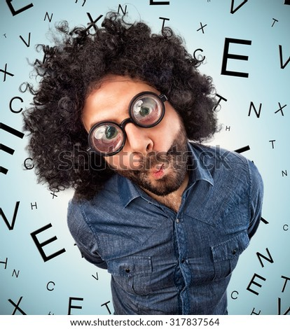 Young man with thick glasses on background with letters for checking eyesight - stock photo