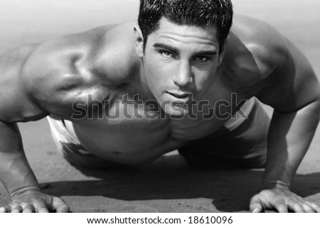 young man with torso doing push-ups on the beach