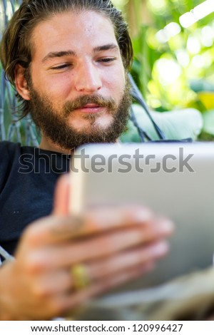 young man with touchpad in hammock